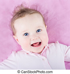 Portrait of a beautiful baby girl on pink background