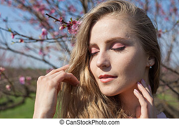 Portrait of a beautiful blonde girl with eyes closed