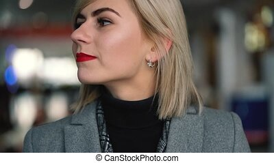 Portrait of a beautiful blonde girl with red lips. Lively...