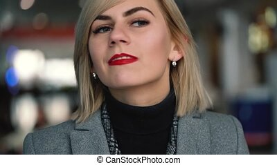 Portrait of a beautiful blonde girl with red lips. Slow motion