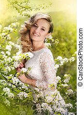 Portrait of a beautiful blonde woman in a blossoming garden