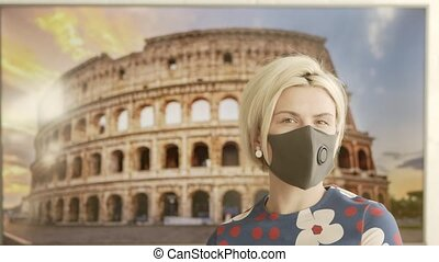 Portrait of a Beautiful Blonde Young Woman Wearing Protective Medical Face Mask and Standing in front of The Colosseum. Safe and Happy Woman Practicing Social Distancing. Online Travel Concept.