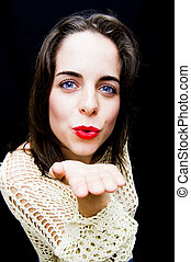 Portrait of a beautiful Blue-eyed woman giving a kiss to the air on black background
