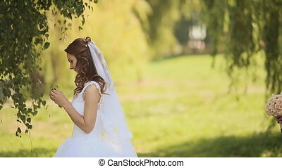 Portrait of a beautiful bride and handsome groom happy together in a birch grove. The groom comes to the bride behind and gives her a bouquet. Joint arms.