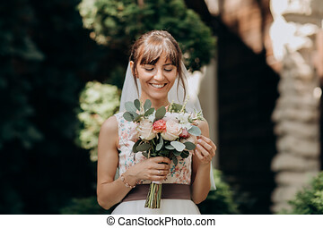 Portrait of a beautiful bride in veil with a bouquet of flowers in his hands