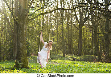 Portrait of a beautiful bride in white wedding dress sitting on swing outdoors