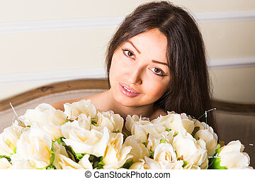 portrait of a beautiful brunette girl with a bouquet of roses