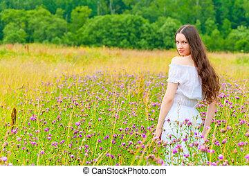 portrait of a beautiful brunette in a field of purple flowers