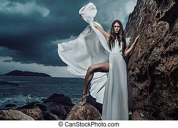 Portrait of a beautiful brunette lady posing on the rock