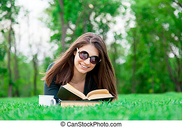 student girl with book on the green grass