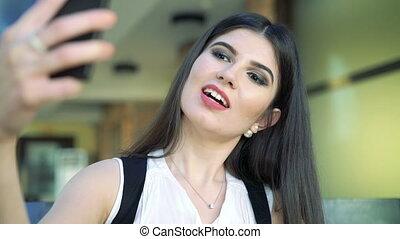 Portrait of a beautiful brunette taking selfie