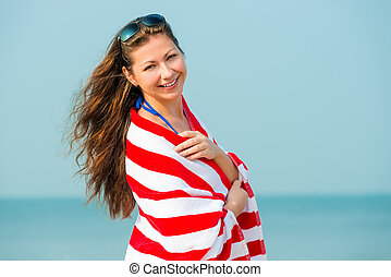 portrait of a beautiful brunette with a towel on the beach