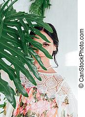 Portrait of a beautiful brunette woman in green plants