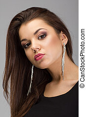Portrait of a beautiful brunette woman with evening make-up and long earrings