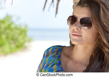 Portrait of a beautiful brunette young woman in aviator sunglasses on a tropical beach leaning against a palm tree, shot outside in natural light