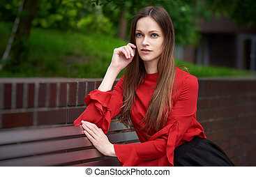 Portrait of a beautiful business woman sitting on a bench