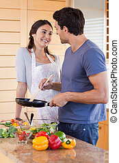 Portrait of a beautiful couple cooking with a pan