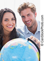 Portrait of a beautiful couple looking at a globe
