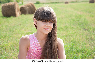Portrait of a beautiful dark-haired girl in a field