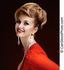 Portrait of a beautiful elegant woman in a red dress with a hairstyle. Red lips. Long earrings. Dark background.