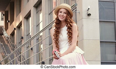 Portrait of a beautiful european woman sitting om steps -...
