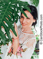 Portrait of a beautiful fashionable brunette woman in a dress with green plants