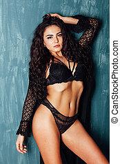 Portrait of a beautiful fashionable brunette woman in black underwear