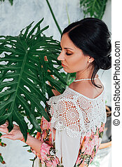 Portrait of a beautiful fashionable brunette woman next to green plants
