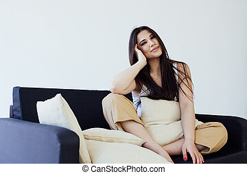 Portrait of a beautiful fashionable brunette woman on a home black sofa