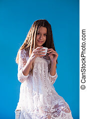 portrait of a beautiful fashionable girl with a cup of tea in white pink clothes