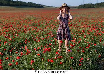 portrait of a beautiful fashionable woman in a field with red flowers