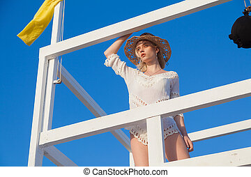 Portrait of a beautiful fashionable woman on the beach by the ocean
