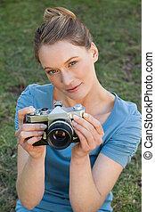 Portrait of a beautiful female photographer at park