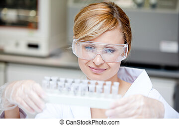 Portrait of a beautiful female scientist holding different samples in her laboratory