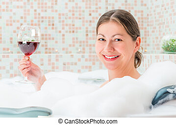 portrait of a beautiful girl in a bath with a glass