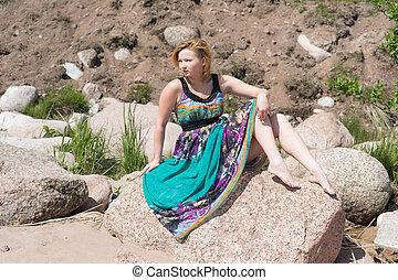 girl in a dress on a rock