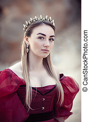 Portrait of a beautiful girl in a red dress and a crown