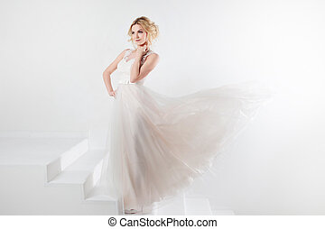 Portrait of a beautiful girl in a wedding dress. Bride, white background, free space on the right