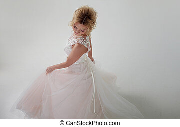 Portrait of a beautiful girl in a wedding dress. Dancing Bride, white background. Top view