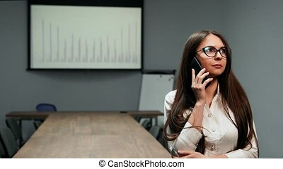 Portrait of a beautiful girl in office clothes standing in a conference room with glasses talking on a mobile phone in the office against the background of schedules