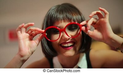 Portrait of a beautiful girl in red glasses at a kinky party.