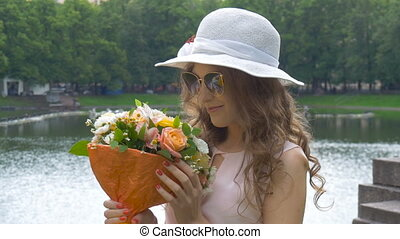 Portrait of a beautiful girl in sunglasses and a white hat with flowers. close-up