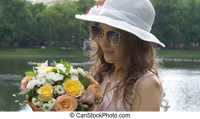 Portrait of a beautiful girl in sunglasses and a white hat with flowers.