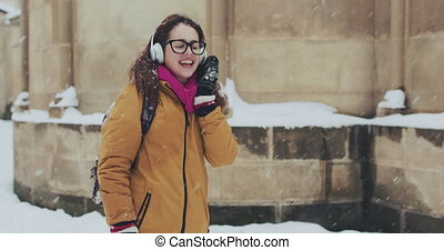 Portrait of a beautiful girl. Listening to music in the snowy city