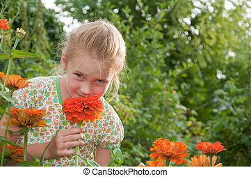 Portrait of a beautiful girl on the background of flowers
