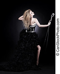 portrait of a beautiful girl singer in black dress with microphone
