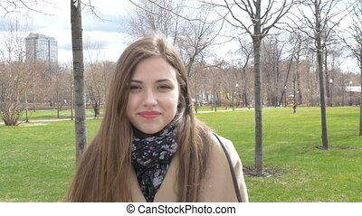 Portrait of a beautiful girl. Smiling walks in the park on a sunny day. Good mood.