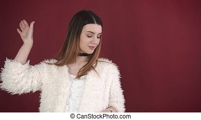 Portrait of a beautiful girl who played with her hair and looking at the camera on a red background