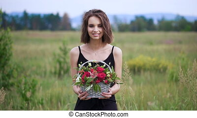 Portrait of a beautiful girl with a basket of flowers in their hands.