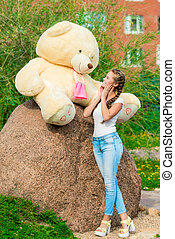portrait of a beautiful girl with a huge bear in the park